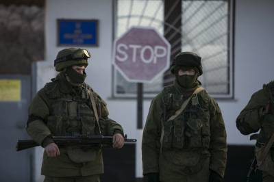 Military personnel, believed to be Russian servicemen, walk outside the territory of a Ukrainian military unit in the village of Perevalnoye March 3, 2014. PHOTO: REUTERS