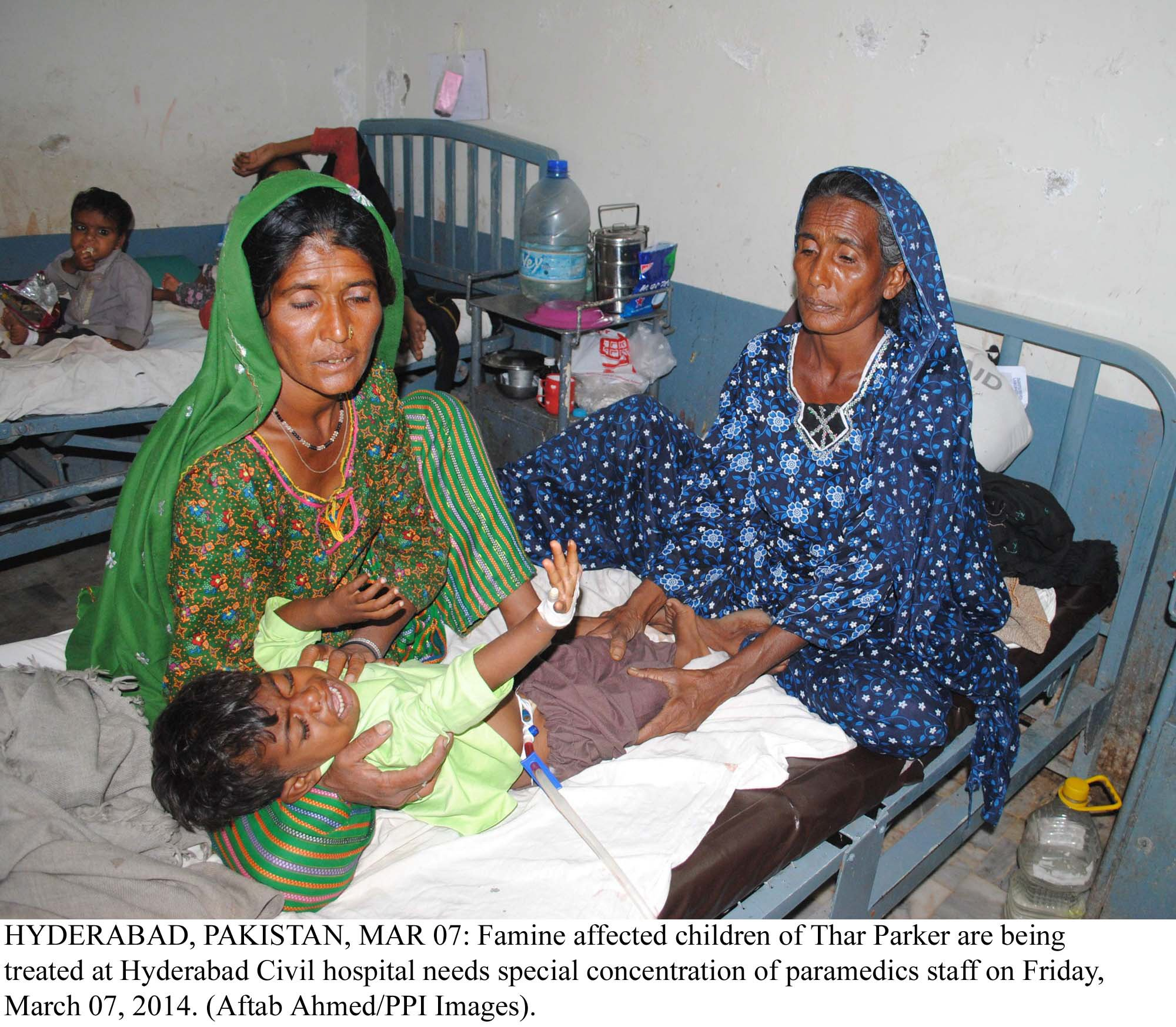 two women from thar watch as a child cries out photo ppi