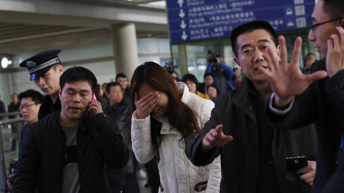 A relative of a passenger onboard Malaysia Airlines flight MH370, covers her face as she cries at the Beijing Capital International Airport on March 8, 2014. PHOTO: REUTERS