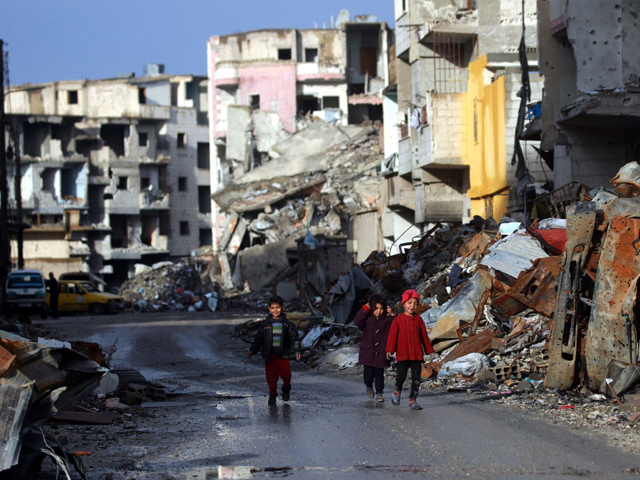 Syrian children walk along a destroyed street in Raqqa, the former de facto capital of the Islamic State (IS) group, on February 18, 2018. PHOTO: AFP