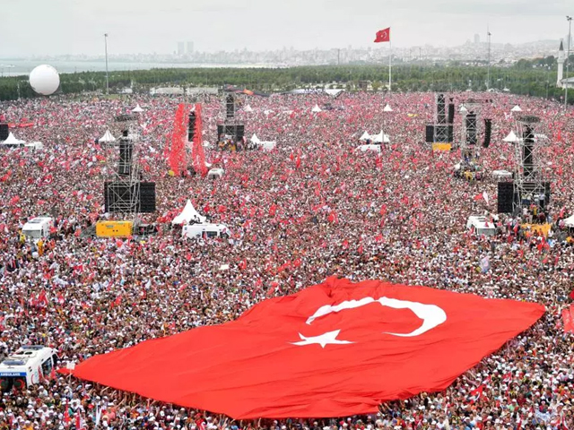Supporters hold a giant Turkish flag during an election rally in Ankara. PHOTO: AFP