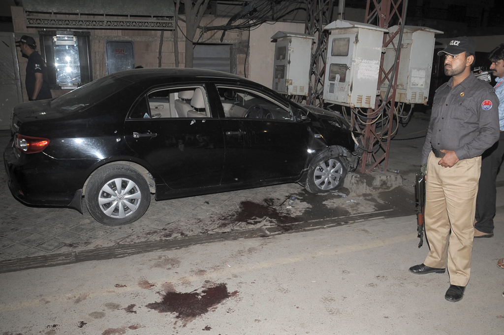 Police official standing near Raza Rumi's vehicle  after he was attacked on Friday evening. PHOTO: TARIQ HASAN/EXPRESS