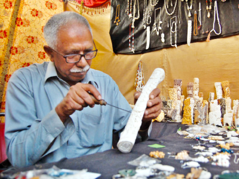 Qureshi applying finishing touches to a decoration piece at his stall at Lok Mela. PHOTO: MUHAMMAD JAVAID/EXPRESS