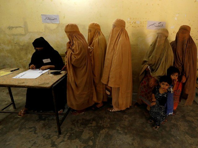 Women, clad in burqas, stand in line to cast their ballot at a polling station during general election in Peshawar.PHOTO: REUTERS