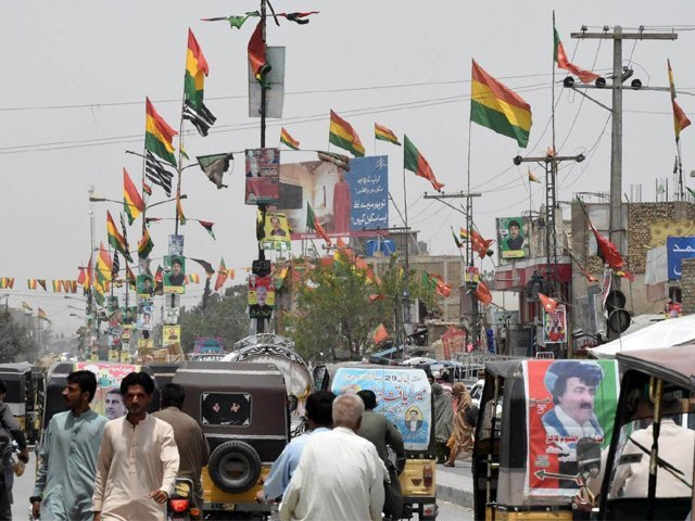 in this picture taken on july 16 2018 pakistani commuters drive along a road with posters of candidates taking part in the upcoming general elections in quetta photo afp