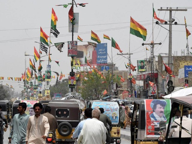 In this picture taken on July 16, 2018, Pakistani commuters drive along a road with posters of candidates taking part in the upcoming general elections, in Quetta. PHOTO: AFP