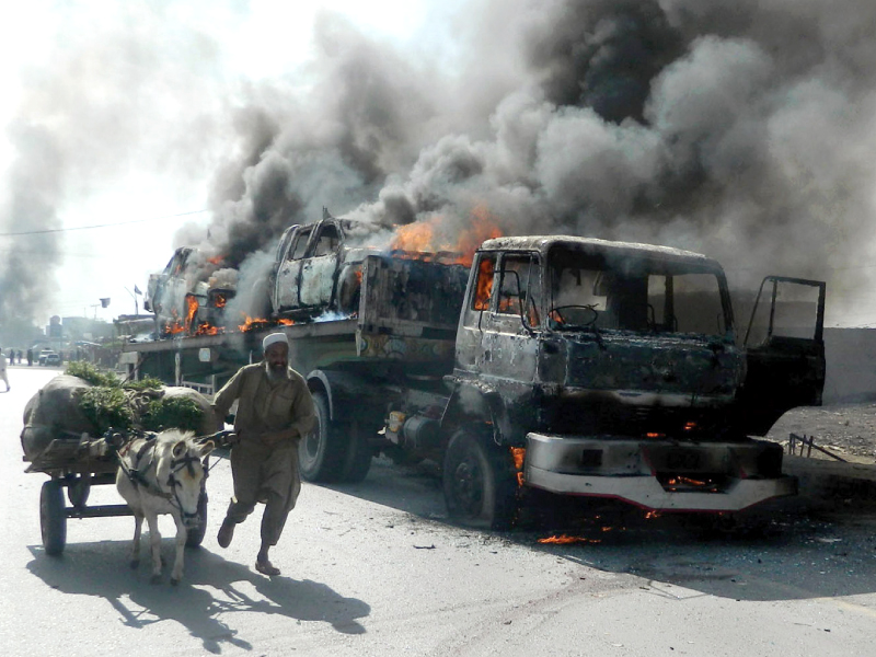 a man leads his donkey cart past a burning truck transporting nato vehicles photo afp file