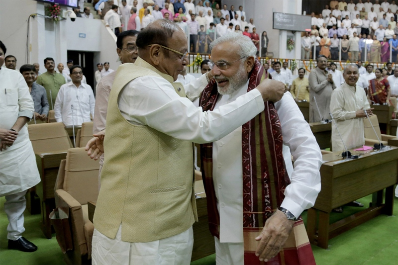 The leader of Opposition (Congress), Shankersinh Waghela (L) gifts a traditional Khes or a shawl to Indian Prime Minister-Elect, Narendra Modi during a special farewell session of Gujarat Assembly  in Gandhinagar. PHOTO: AFP