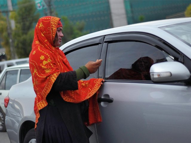 A transgender woman begs for alms from motorists at a traffic stop in Rawalpindi, outside Islamabad, Pakistan, on March 27. PHOTO: AFP