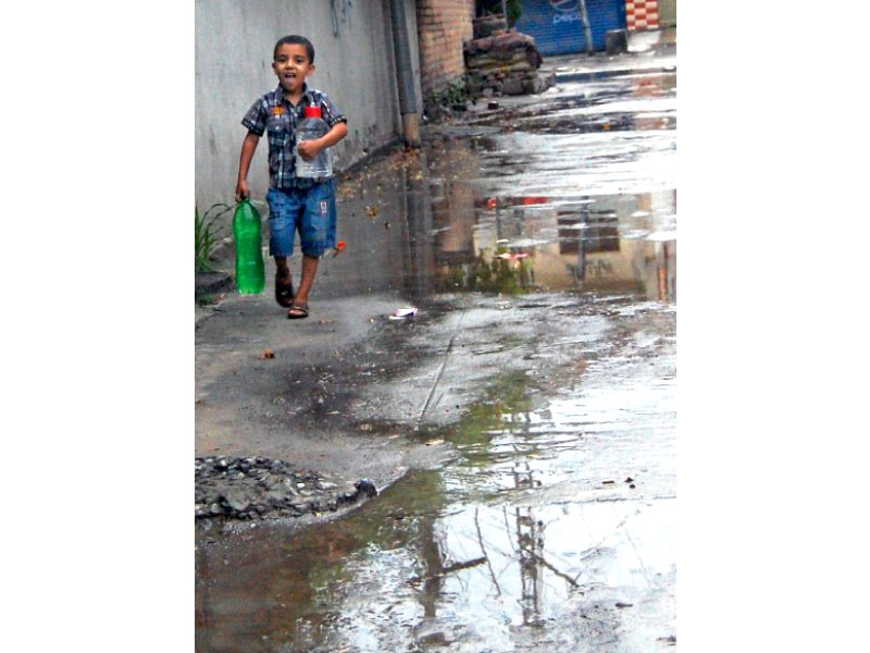 a boy juggles with bottles while fetching drinking water from a filtration plant as the twin cities received first pre monsoon rain on wednesday photo muhammad javaid express