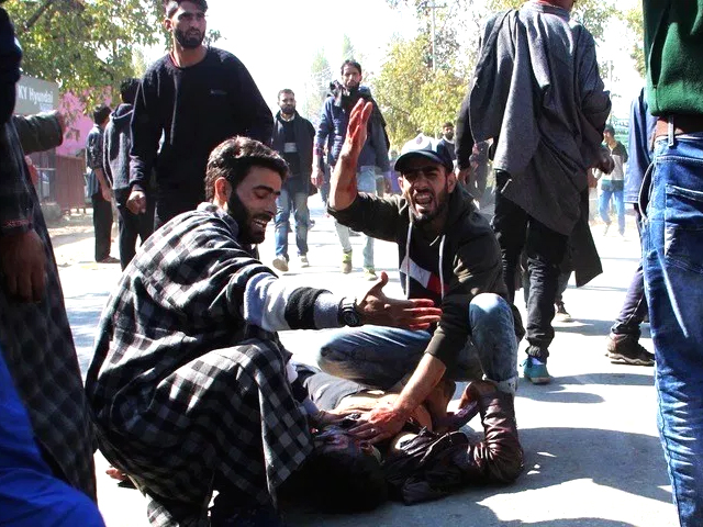 Kashmiri men gesture as another lies on the ground after a blast near a residential house in Kulgam on October 21, 2018. PHOTO: AFP