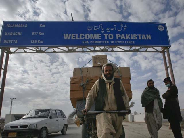 A Pakhtun man passes a road sign while pulling supplies toward the Pakistan-Afghanistan border crossing in Chaman. PHOTO: REUTERS