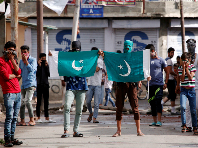 Kashmiri protesters hold the flag of Pakistan during a protest in Srinagar against the recent killings in IoK. PHOTO: REUTERS