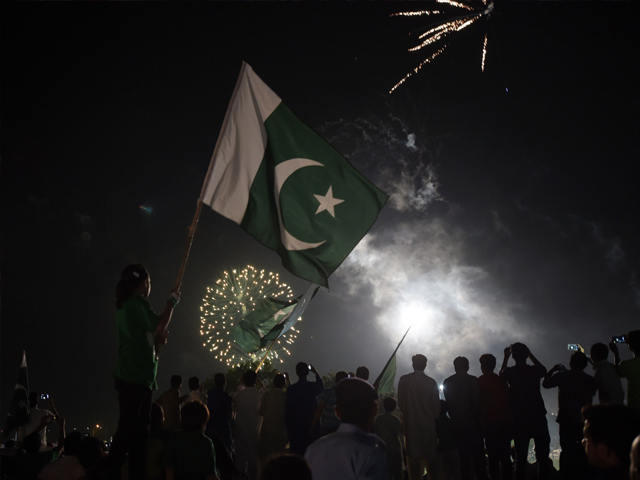 Residents carry national flags as they watch fireworks in Islamabad on August 14, 2017, to mark Independence Day. PHOTO: AFP