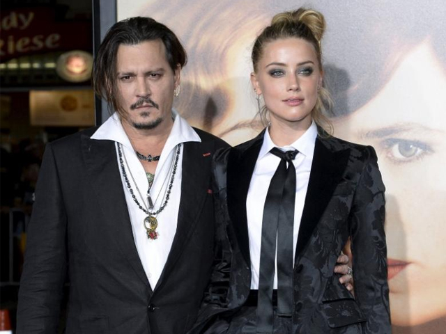 """Cast member Amber Heard and husband Johnny Depp pose during the premiere of the film """"The Danish Girl,"""" in Los Angeles, California November 21, 2015. PHOTO: REUTERS"""