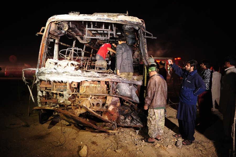 Pakistani volunteers search for victims inside a burnt out passenger bus after it collided with an oil tanker along the Super Highway near Karachi early on January 11, 2015. PHOTO: AFP