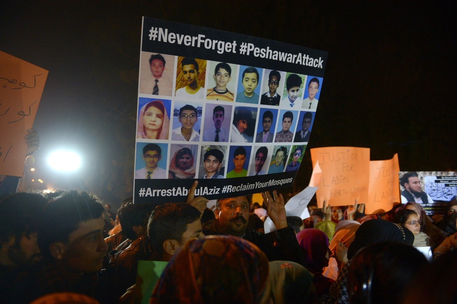 A protester carries a placard during a protest by civil society activists in Islamabad featuring pictures of students who died in the Peshawar school attack. PHOTO: AFP
