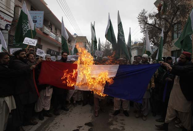 People burn the French flag in a protest against satirical French weekly newspaper Charlie Hebdo in Quetta. PHOTO: REUTERS