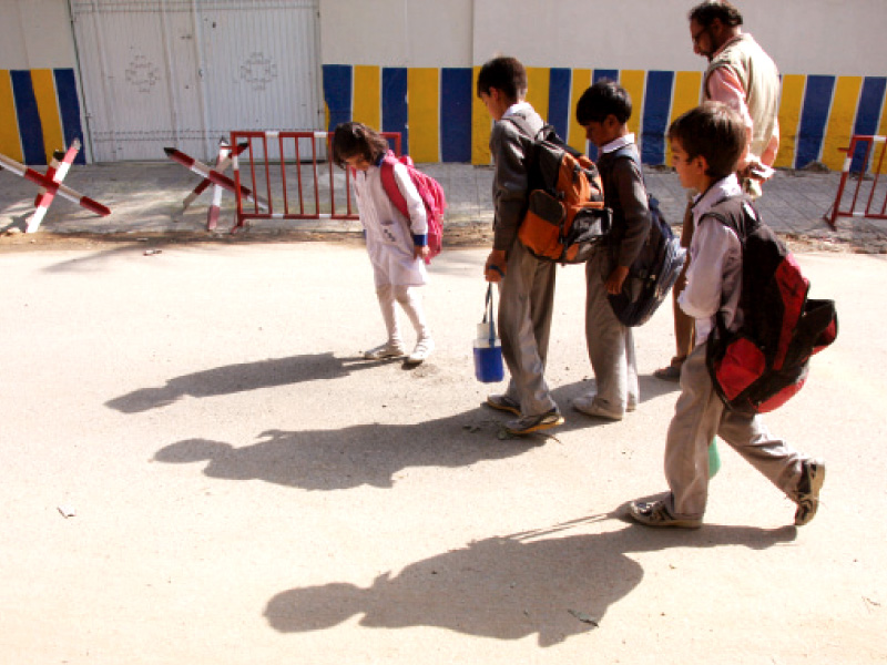 students walk outside beacon light academy where two grenades were hurled on tuesday photo athar khan express