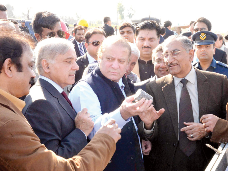 prime minister nawaz sharif and punjab cm shahbaz sharif inspect a piece of iron ore at the site of excavation in chiniot photo ppi