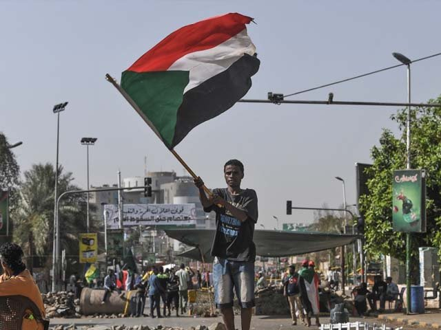 A Sudanese protester waves a national flag near a makeshift barricade. PHOTO: GETTY