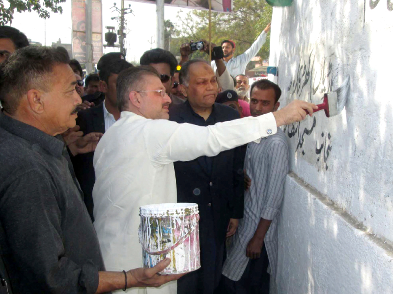 Sharjeel Memon removes wall chalking during the clean Karachi campaign. PHOTO: PPI