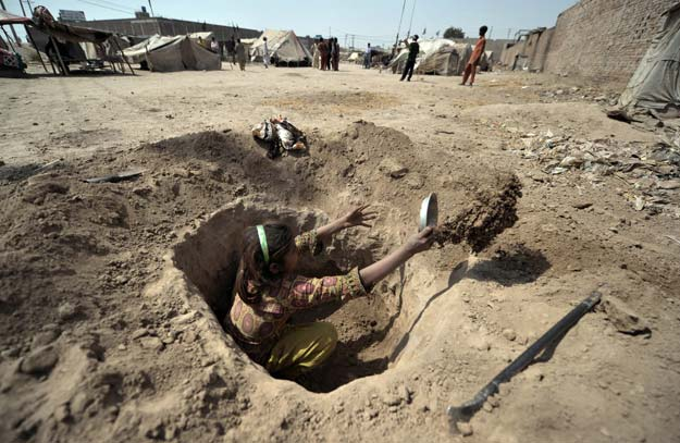a pakistani child digs a hole to be used as a toilet for her family at a slum in multan on march 13 2012 photo afp