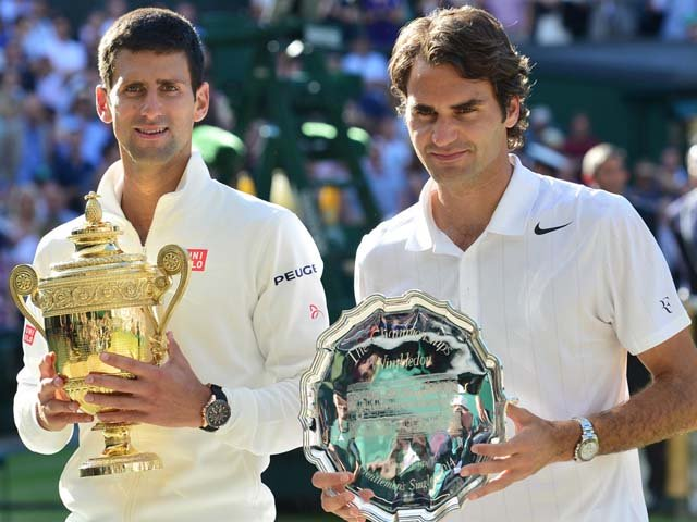 Novak Djokovic, left, shows off the winner's trophy after defeating Roger Federer in the men's final at Wimbledon 2014. PHOTO: AFP