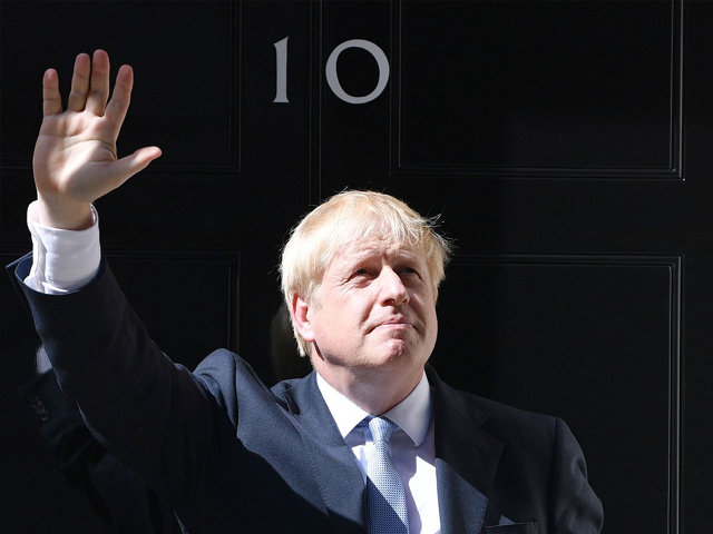 New British Prime Minister Boris Johnson waves from the door of No. 10 Downing Street . PHOTO: GETTY