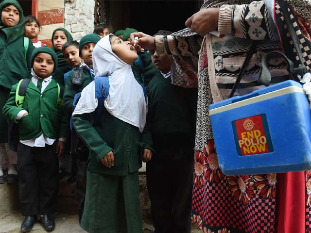 A Pakistani health worker administers polio vaccine drops to school children. PHOTO: GETTY
