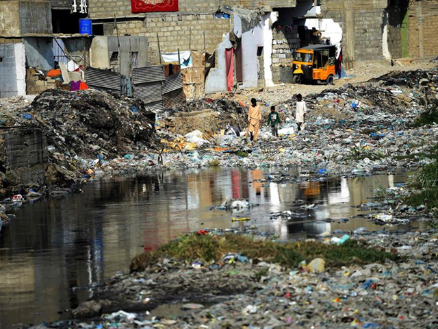 citizens walk amongst dumped garbage at a residential area of karachi photo afp