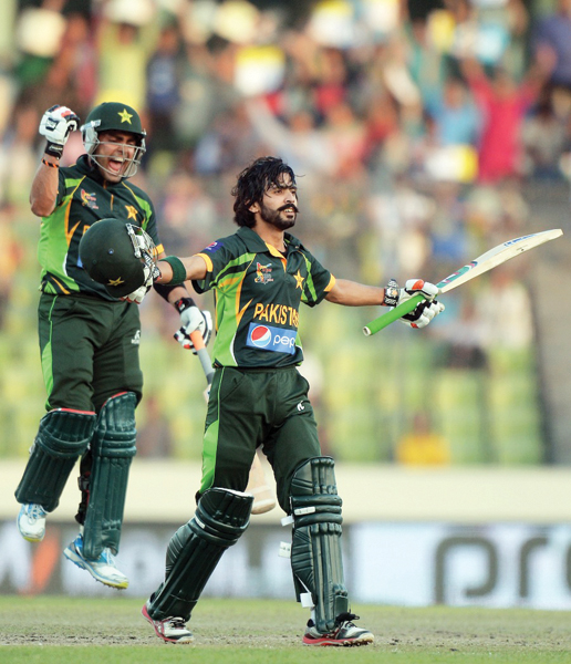 A file photo of Fawad Alam celebrating victory with Umar Akmal in the background. PHOTO: AFP