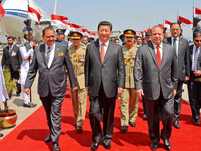 chinese president xi jinping accompanied by his pakistani counterpart mamnoon hussain and prime minister nawaz sharif walks out of the nur khan airbase in rawalpindi photo pid