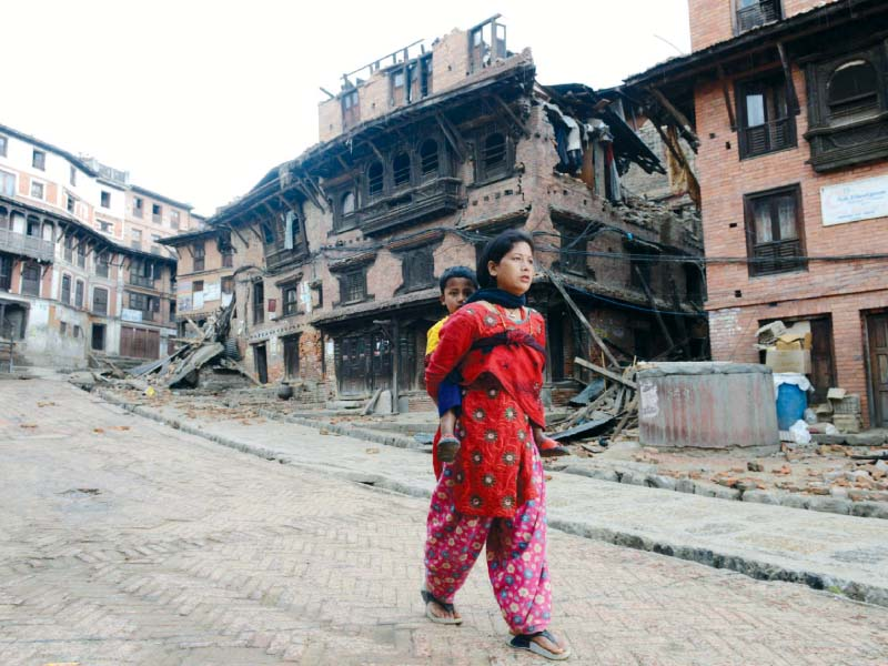 a woman carries a child next to collapsed houses on the outskirts of kathmandu photo afp