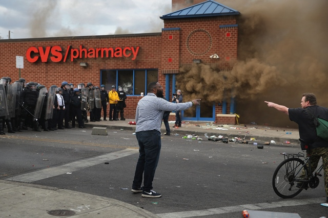 Two men argue opposing views as a CVS pharmacy burns at the corner of Pennsylvania and North avenues during violent protests following the funeral of Freddie Gray April 27, 2015 in Baltimore, Maryland. PHOTO: AFP