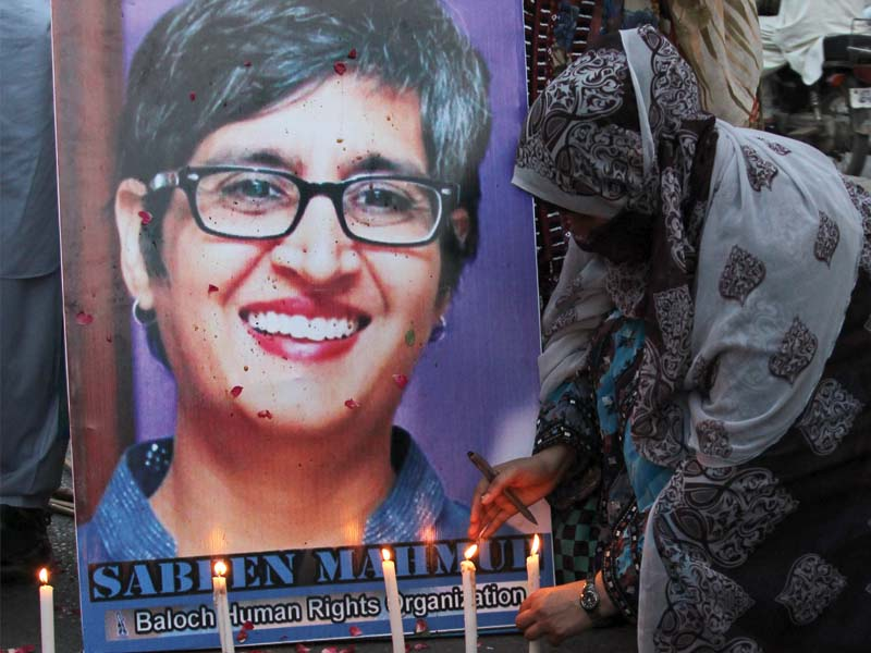 a woman lights a candle in front of a poster of slain activist sabeen mahmud members of civil society gathered at karachi press club on tuesday to protest her murder photo aysha saleem express