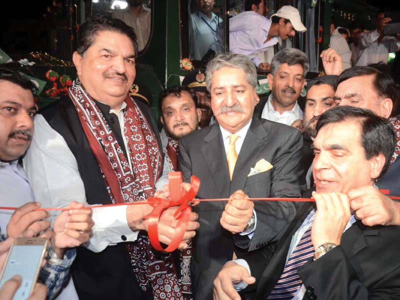 MNA Syed Naveed Qamar cuts the ribbon to launch the new Green Line rail service from Karachi to Islamabad. PHOTO: APP