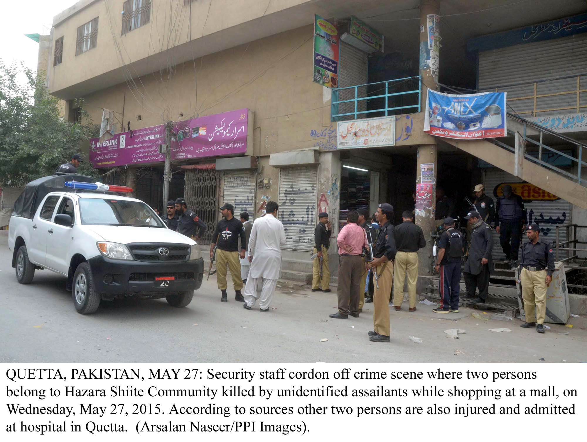 police officials gather outside the store where two hazara men were gunned down on wednesday photo ppi