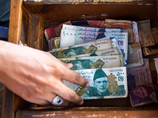 a pakistani man counts pakistan 039 s rupees at his shop in karachi photo getty