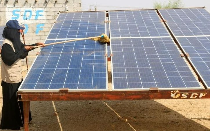 a yemeni woman cleans a solar panel at the friends of the environment station photo afp