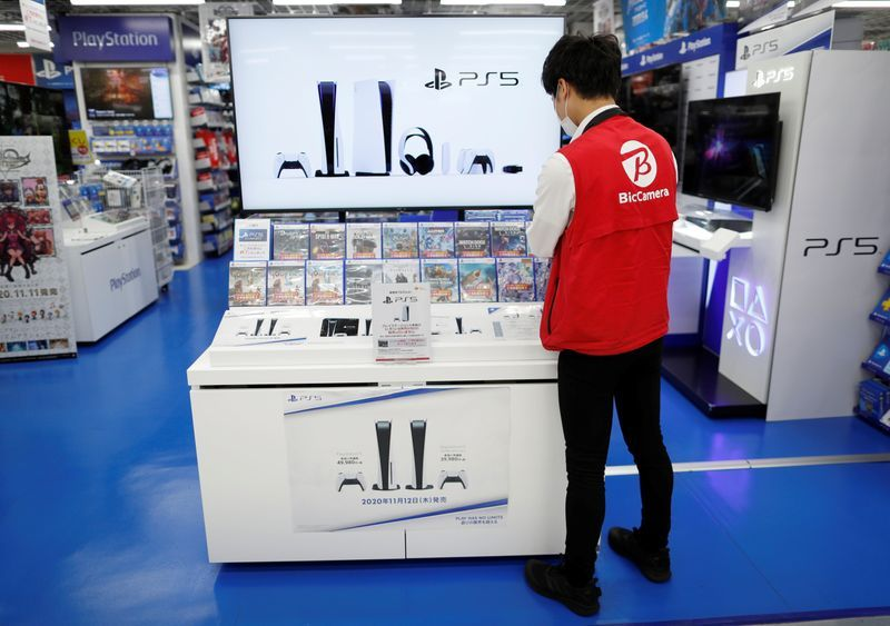 an employee of the consumer electronics retailer chain bic camera works at the promotion display for the sony playstation 5 game console and its gaming softwares in tokyo japan november 10 2020 photo reuters