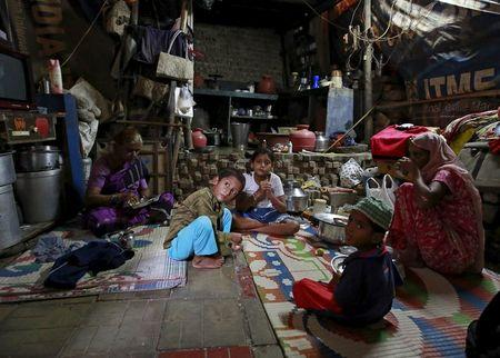 family members of mehboob sheikh 45 who died after consuming bootleg liquor sit inside their house at a slum in mumbai india june 20 2015 photo reuters
