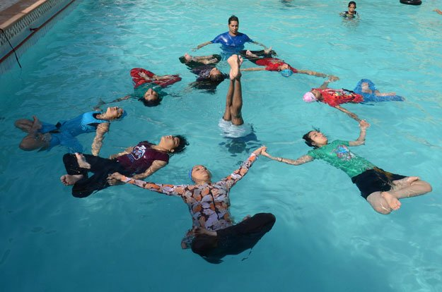 Indian children perform water yoga as they take part in a mass yoga session to mark the International Yoga Day at Dau ri Dhani Swiming Pool in Jodhpur on June 21, 2015. PHOTO: AFP