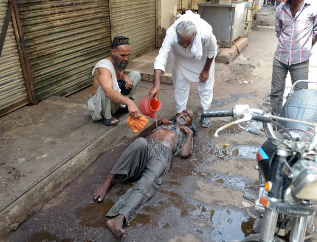 a resident helps a heatstroke victim at a market area during a heatwave in karachi on june 23 2015 photo afp