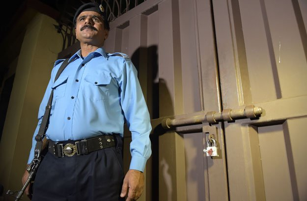 a policeman stands guard outside the office of the international charity save the children sealed by order of authorities in islamabad on june 11 2015 photo afp