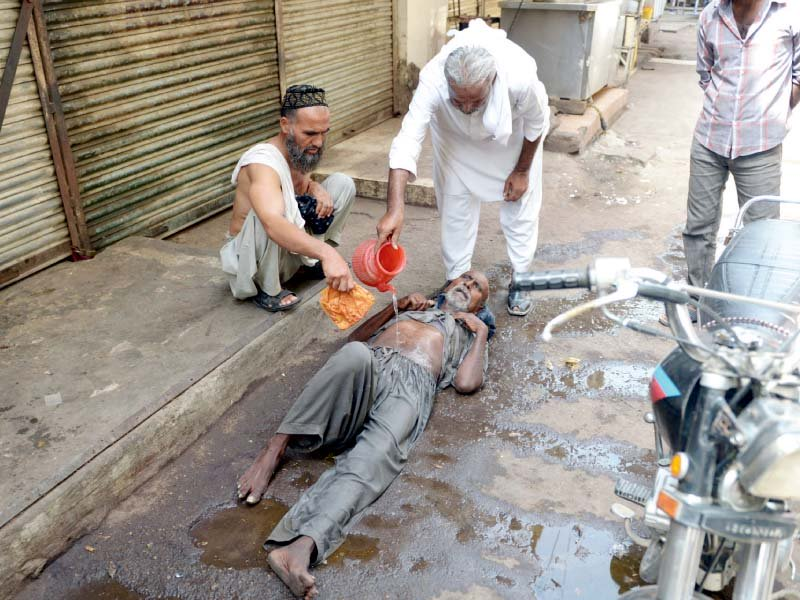 People help a heatstroke victim at a market in Karachi. PHOTO: AFP