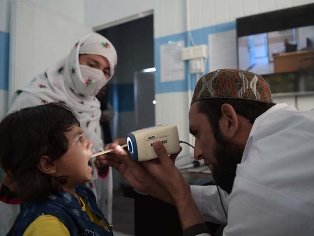 A Pakistani paramedic checks a child's throat at a telemedicine online treatment centre. PHOTO: AFP