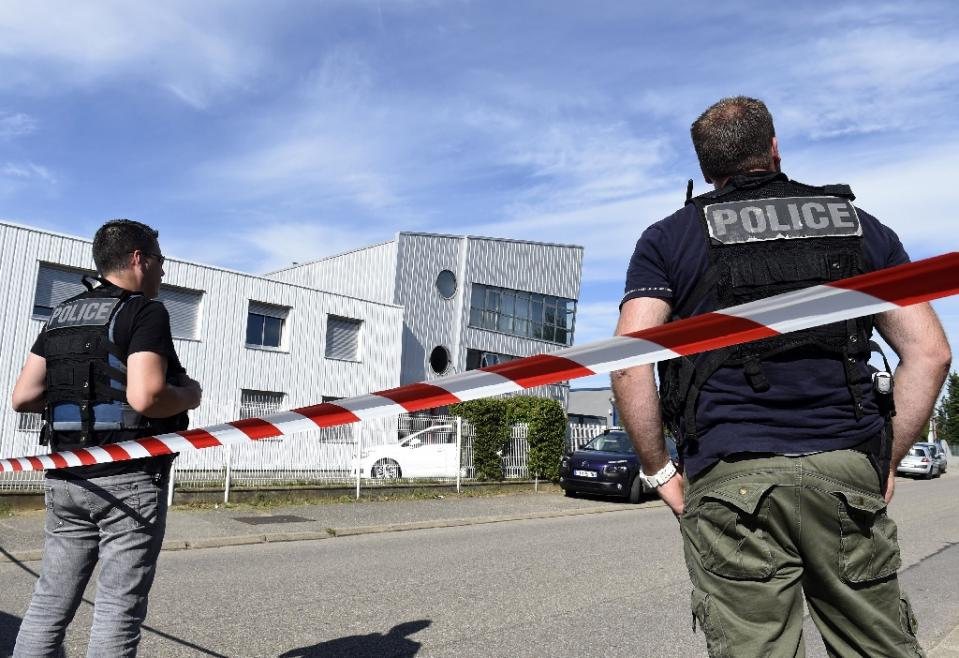 french police officers stand guard near a cordon outside the delivery service company in chassieu on june 26 2015 where the victim who was decapitated worked photo afp