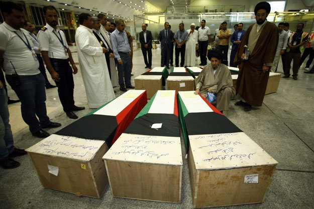 muslim clerics gather over the coffins of eight kuwaitis who lost their lives during the suicide bombing on the al imam al sadeq mosque bombing in kuwait upon their arrival for burial in the holy iraqi city of najaf on june 27 2015 photo afp