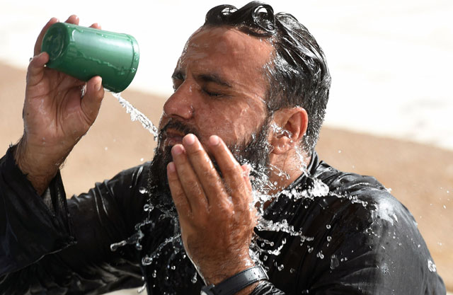 a man cools down with water at a mosque during a heatwave in karachi on june 22 2015 photo afp